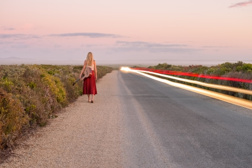 Beautiful girl musician walking down a secluded road at sunset with her guitar and a car driving by.